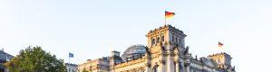 Bundestag in Berlin mit wehender Deutschland-Flagge